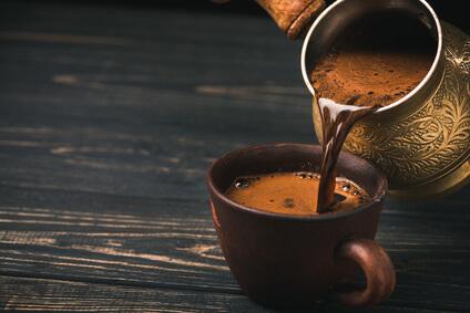 Türkischer Kaffee wird vom Cezve-Kännchen in eine Tasse geschenkt