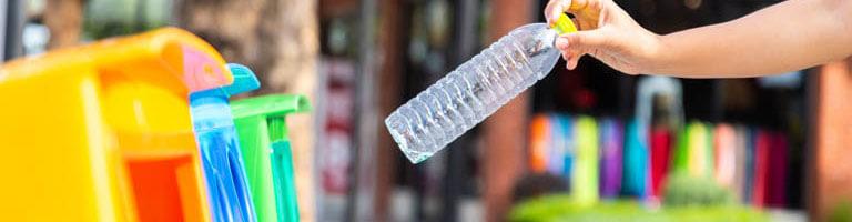 Plastikflasche wird in Mülleimer geworfen