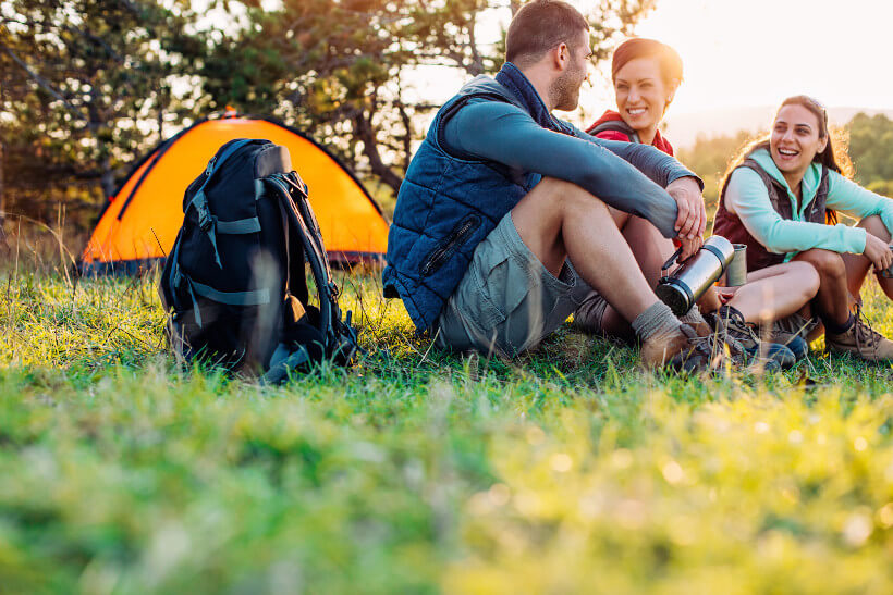 Ein Mann und zwei Frauen sitzen neben einem schwarzen Rucksack und vor einem orangen Zelt auf dem Rasen