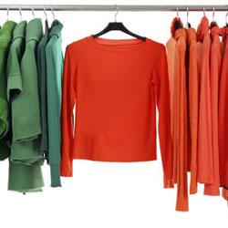 Kleidung in verschiedenen Farbtönen auf Kleiderbügeln aufgehaengt auf einer Stange