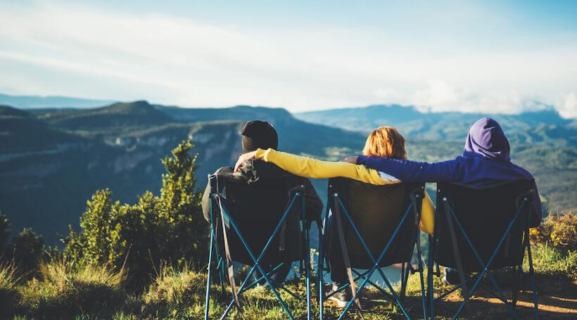 Drei Menschen sitzen auf Campingstühlen nebeneinander auf einem Berg und schauen in die Ferne