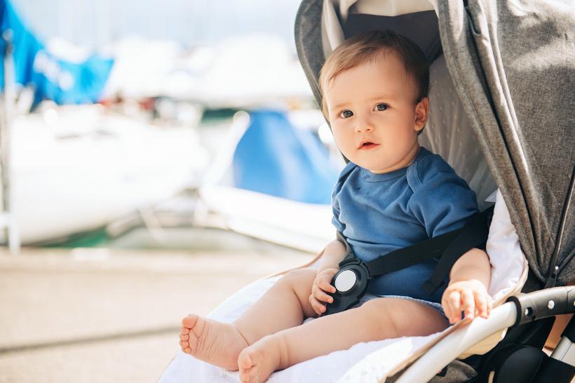 Ein Kleinkind sitzt aufrecht in einem Buggy und schaut in die Kamera. Es hat nur einen Strampler an und nackt Füße. Im Hintergrund ist eine Strandszene zu erkennen, die Sonne scheint.