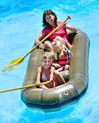 Frau sitzt mit zwei Mädchen, circa sieben Jahre alt, in einem kleinen, aufblasbaren Schlauchboot. Sie und eines der Kinder hält ein Paddel ins Wasser. Das Wasser um sie herum ist Poolwasser. Alle drei lächeln.