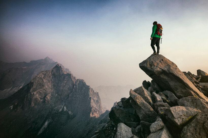 Mann mit einem Rucksack und einer grünen Jacke steht auf einem Felsen und schaut in die Ferne