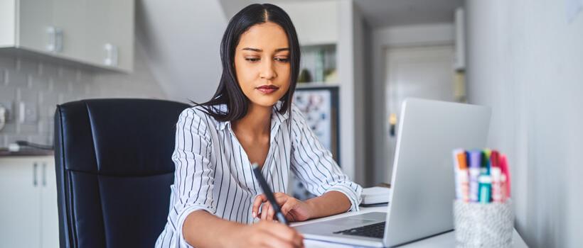 Frau sitzt an Laptop im Homeoffice