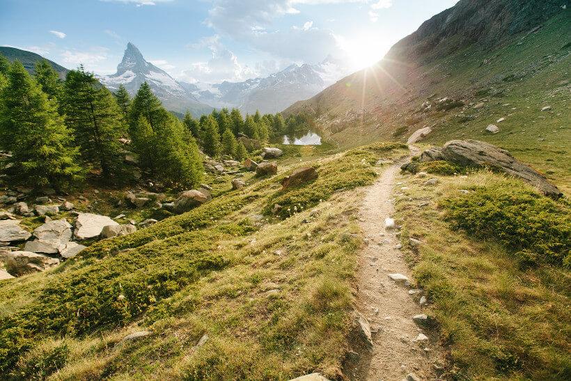 Wanderpfad in den Bergenen mit Bergspitzen im Hintergrund auf die die Sonne scheint