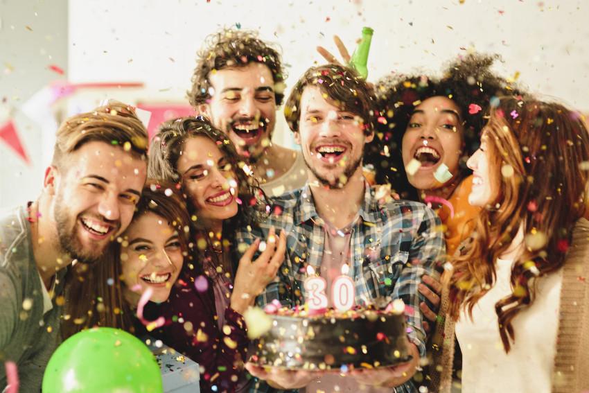 Verschiedene fröhliche Menschen mit Geburtstagstorte im Konfettiregen