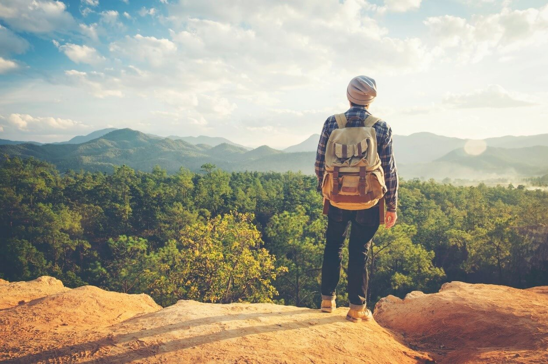 Ein Mann mit grauer Mütze und braunem Rucksack steht auf einem Steinfelsen und schaut über einen Nadelwald in die Ferne