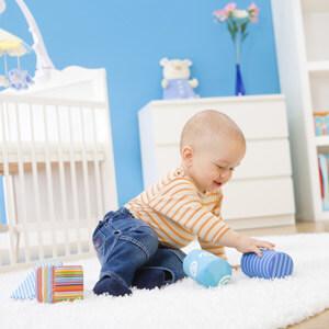 Kind spielt mit Babyspielzeug