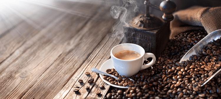 Handkaffeemühle aus Metall zwischen Kaffeebohnen