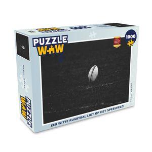 Puzzle 1000 Teile - Ein weißer Rugbyball liegt auf dem Spielfeld